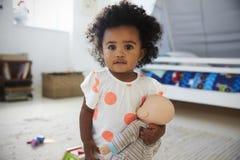 使用与在游戏室的玩偶的女婴画象 免版税库存图片