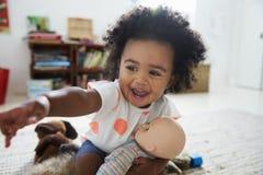 使用与在游戏室的玩偶的愉快的女婴 免版税库存照片