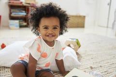 使用与在游戏室的玩具的愉快的女婴画象  库存照片