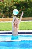 使用与在游泳池的一个球的小男孩 免版税库存照片