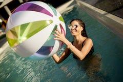 使用与在游泳池的一个球的少妇 库存照片