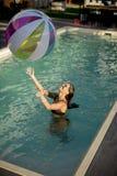 使用与在游泳池的一个球的少妇 免版税库存图片