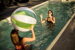 使用与在游泳池的一个球的少妇 免版税库存照片