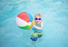 使用与在游泳池的海滩球的逗人喜爱的小男孩 免版税库存图片