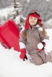 使用与在滑雪节假日的爬犁的女孩 免版税库存照片