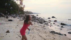 使用与在热带海滩的肥皂泡的愉快的深色的妇女在日落时间 慢的行动 1920x1080 股票录像