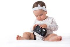 使用与在白色背景的照相机的美丽的女婴 免版税库存照片