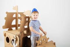 使用与在白色背景的纸板船的小男孩 库存照片