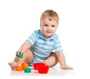 使用与在空白背景的玩具的逗人喜爱的男婴 免版税图库摄影