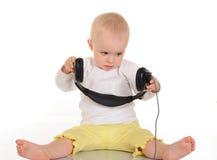 使用与在空白背景的耳机的婴孩 免版税库存图片