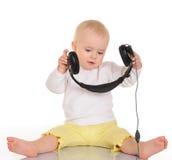 使用与在空白背景的耳机的婴孩 免版税库存照片
