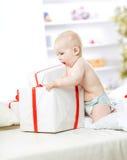 使用与在箱子的购物的一个岁逗人喜爱的婴孩在沙发 免版税库存照片