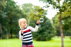 使用与在绿色夏天同水准的肥皂泡的小白肤金发的女孩 免版税库存照片