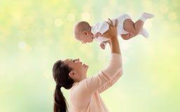 使用与在绿色的小婴孩的愉快的母亲 免版税库存图片
