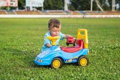 使用与在绿草的一辆大玩具汽车的孩子 库存图片