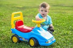 使用与在绿草的一辆大玩具汽车的孩子 免版税库存照片