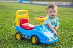 使用与在绿草的一辆大玩具汽车的孩子 免版税图库摄影