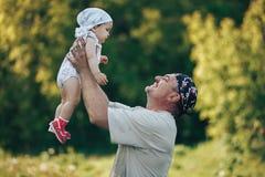 使用与在自然背景的可爱的女婴的年轻祖父 祖父母和孙悠闲时间概念 免版税库存图片