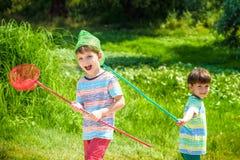使用与在草甸的瓢网的两个小兄弟姐妹兄弟在温暖和晴朗的夏天或春日 库存图片