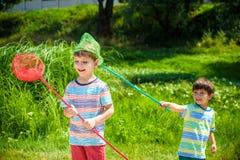 使用与在草甸的瓢网的两个小兄弟姐妹兄弟在温暖和晴朗的夏天或春日 免版税库存图片