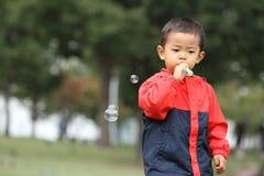 使用与在草的泡影的日本男孩 库存照片