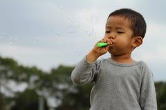 使用与在草的泡影的日本男孩 库存图片