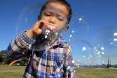 使用与在草的泡影的日本男孩 免版税库存照片