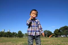 使用与在草的泡影的日本男孩 免版税库存图片