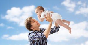 使用与在蓝天的婴孩的愉快的年轻父亲 图库摄影