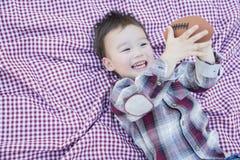 使用与在野餐毯子的橄榄球的年轻混合的族种男孩 库存图片