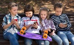 使用与在长凳的电话的孩子户外 免版税库存照片