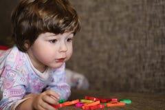 使用与在长沙发的小玩具的孩子在屋子里 库存图片
