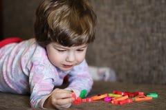 使用与在长沙发的小玩具的孩子在屋子里 免版税库存图片