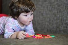 使用与在长沙发的小玩具的孩子在屋子里 库存照片