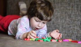 使用与在长沙发的小玩具的孩子在屋子里 免版税库存照片