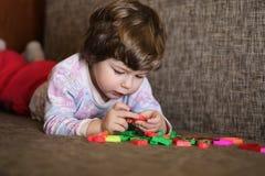 使用与在长沙发的小玩具的孩子在屋子里 免版税图库摄影