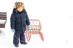 使用与在雪的一个雪撬的新男孩 免版税库存图片