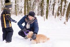使用与在雪的一条狗的愉快的家庭户外 免版税库存照片