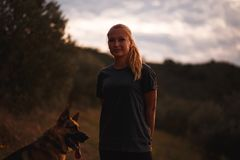 使用与在黄色花的领域的德国牧羊犬狗的白肤金发的女孩 免版税图库摄影