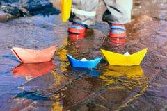 使用与在水水坑的纸小船的孩子 免版税库存照片