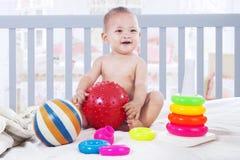 使用与在婴孩小儿床的玩具的快乐的婴孩 库存照片