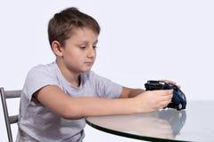 使用与在玻璃桌上的蓝色汽车的男孩 免版税图库摄影