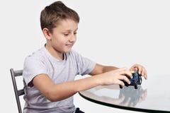 使用与在玻璃桌上的蓝色汽车的男孩 免版税库存照片