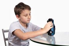 使用与在玻璃桌上的蓝色汽车的男孩 库存图片