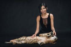 使用与在黑背景的幼狮的美丽的女孩 免版税图库摄影