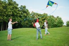 使用与在绿色草坪的风筝的不同种族的孩子在公园 免版税图库摄影