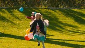 使用与在绿色草甸的五颜六色的气球的滑稽的小女孩 影视素材
