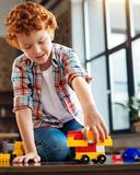 使用与塑料汽车的快乐的男孩在家戏弄 免版税图库摄影
