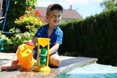 使用与塑料玩具的男孩由游泳池 图库摄影