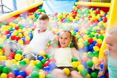 使用与多彩多姿的塑料球的孩子 库存图片